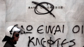 A Greek riot Police officer passes graffiti on the Bank of Greece (Getty Images: Milos Bicanski)