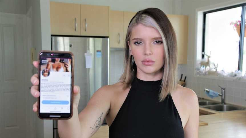 Woman in her 20s holding a mobile phone to the camera with a profile page on the screen. She does not look impressed.