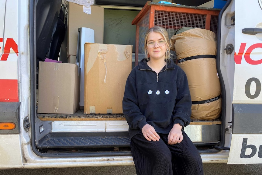 A young woman in a van with moving boxes