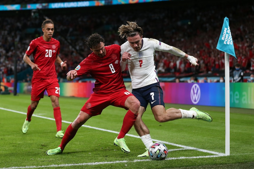 Jack Grealish's hair is flying as he tries to clear a ball in the corner. Thomas Delaney moves in to tackle