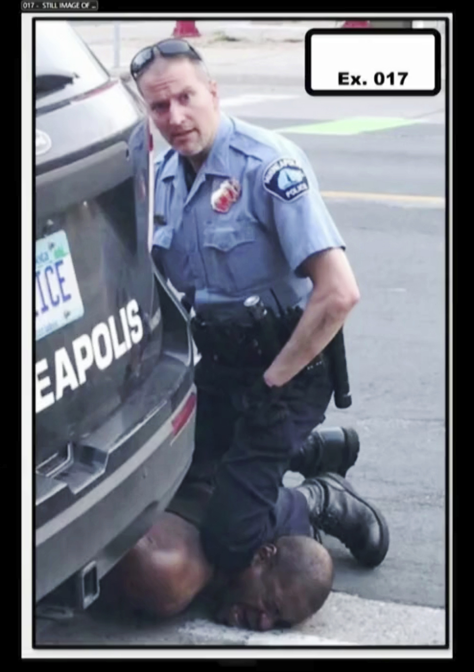A police officer kneels on the neck of George Floyd.
