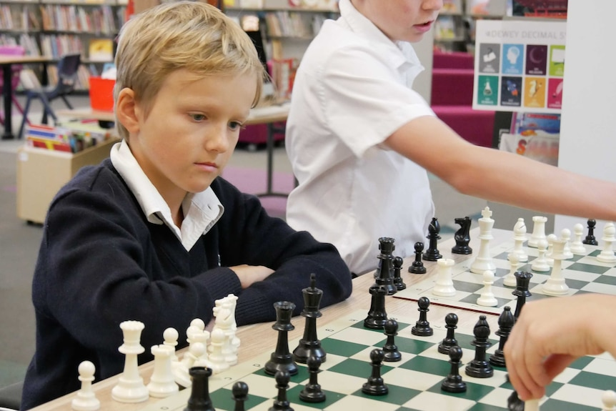 A primary school boy sits at a chess board with a look of concentration.