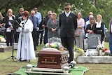 Mourners gather around the coffin of David Routledge, at a cemetery
