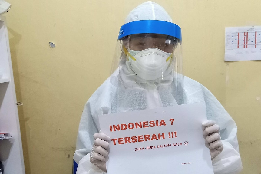 "Indonesian medical worker wearing protective equipment holds sign reading ""Indonesia? Whatever! Do what you like."""