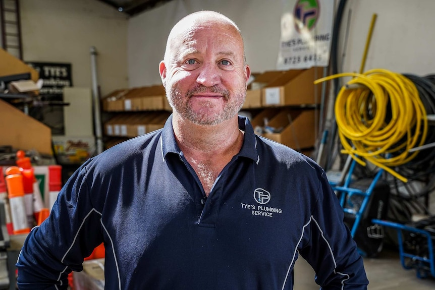 A man wearing a navy polo shirt in a large shed with plumbing gear behind him smiles for a photo.
