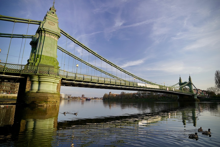 A steel suspension bridge spans the Thames River in London.