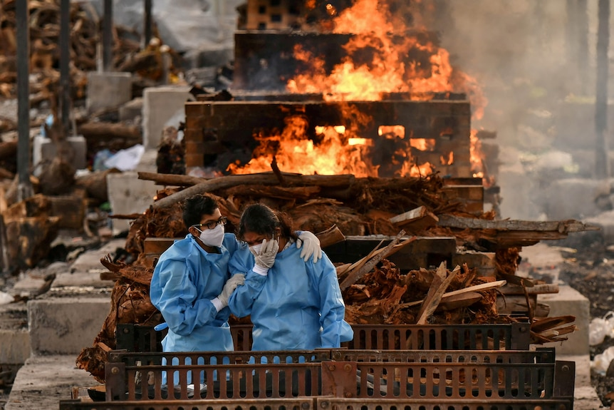 Two people dressed in blue scrubs and wearing masks lean on each other and cry in front of a fire.