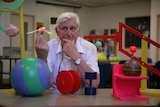 Scientist balances a toy bird on his finger and sits at a desk with various colourful props.
