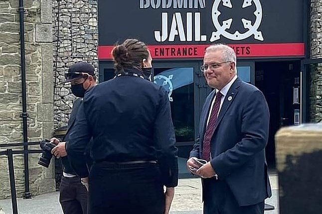 Scott Morrison is mid-conversation with a woman outside the main entrance to an old stone building.
