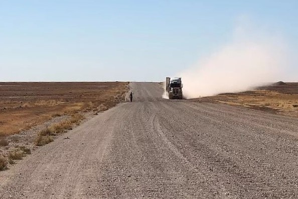 A big truck throws up dust as it passes Phil McDonald on the Eyre Development Road on the way to Bedourie.