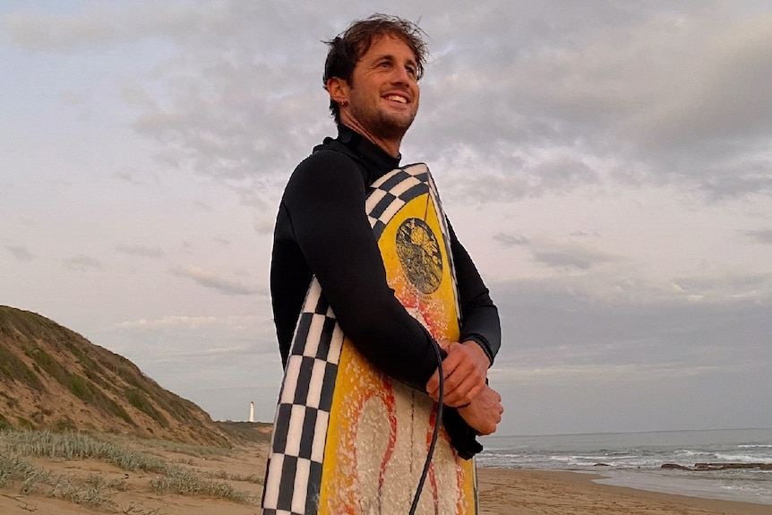 Surfer Joe Draffen with his board on the beach at Fairhaven, Victoria.