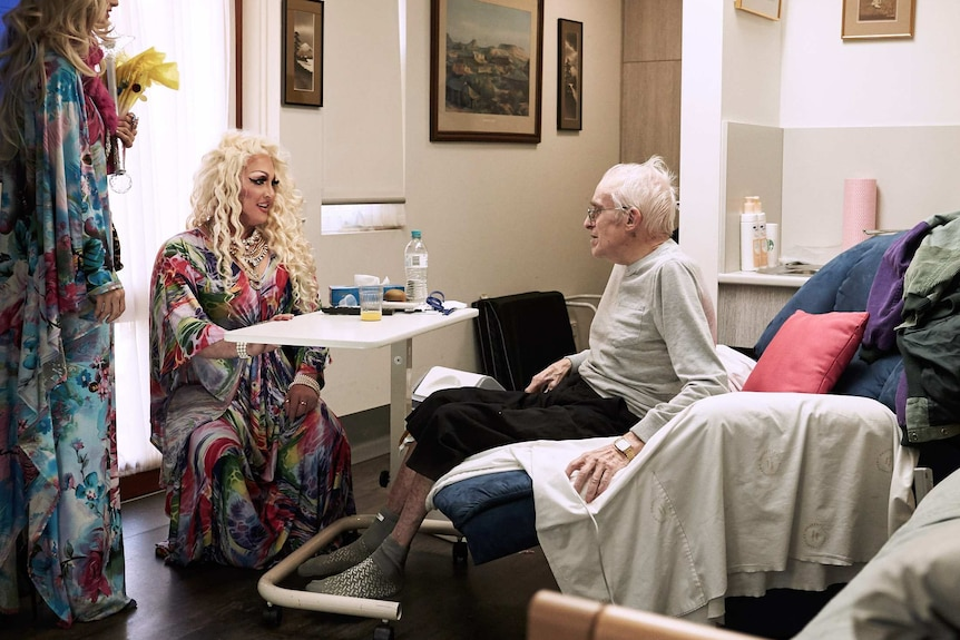 The drag queens talking to a resident in his room, while he sits on his bed.