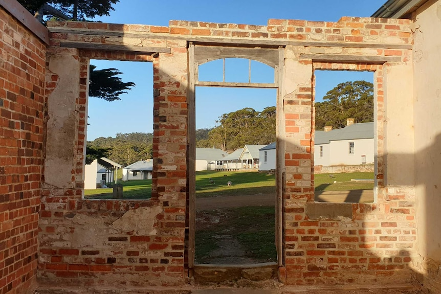 An old brick building looking towards a convict settlement with a wombat and geese in the distance