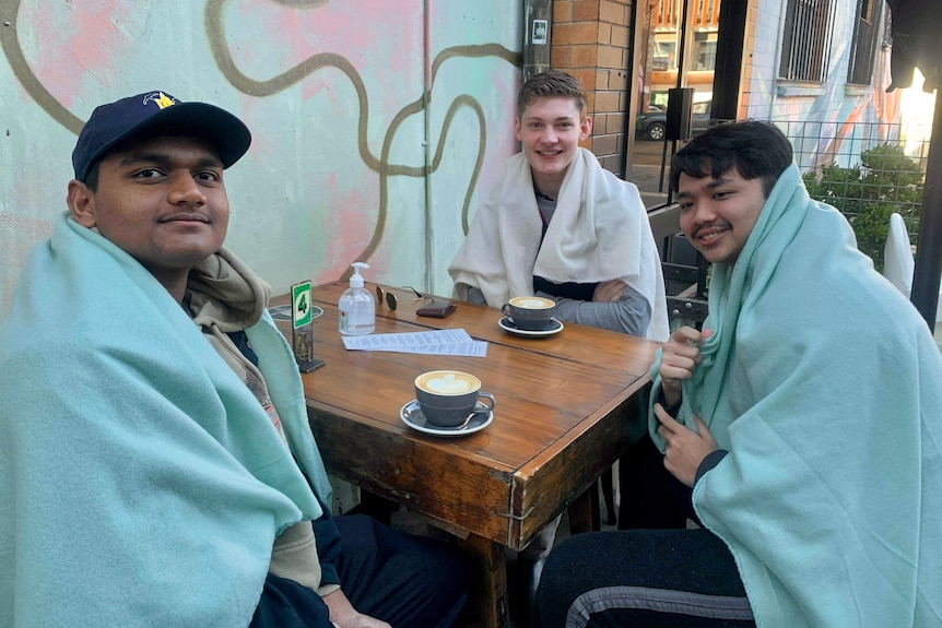 Three young men wrapped in blankets sit at a cafe table and drink coffee.