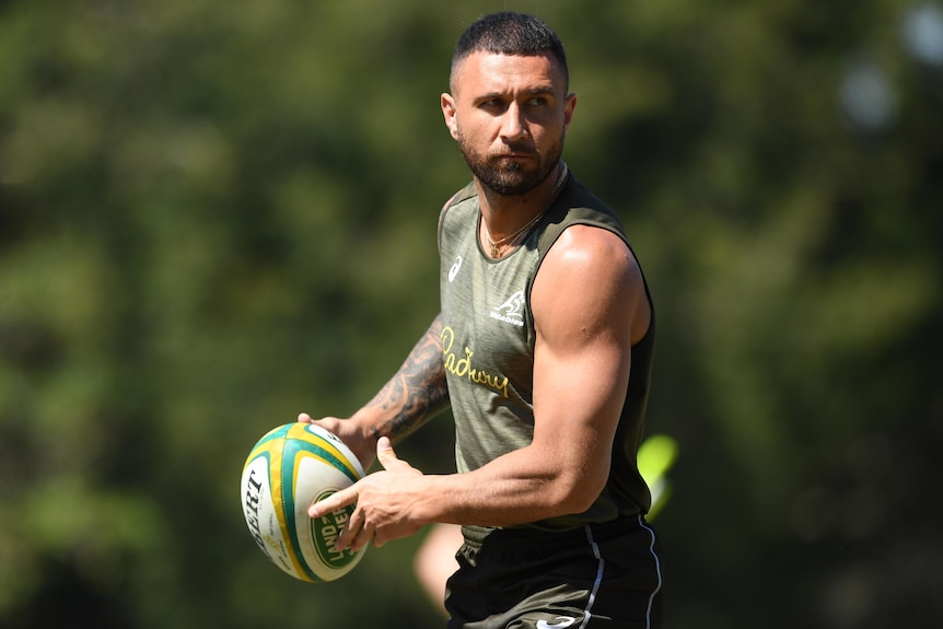 A Wallabies squad member looks to his left as he prepares to pass the ball at a training session.