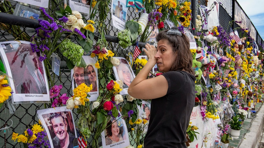 A woman wipes tears from her face as she looks along a chainlink fence adorned with flowers and photos arranged as a vigil.