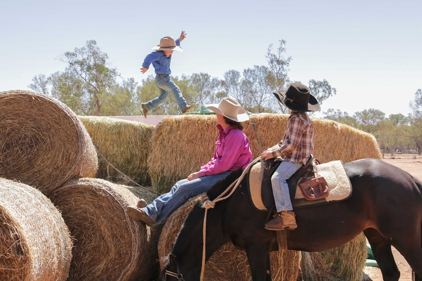 The prow family sitting on a stack of hay donated by the drought appeal