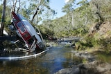 A damaged helicopter in a river bed in a national park.