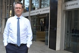 Guy Debelle stands outside the Reserve Bank head office