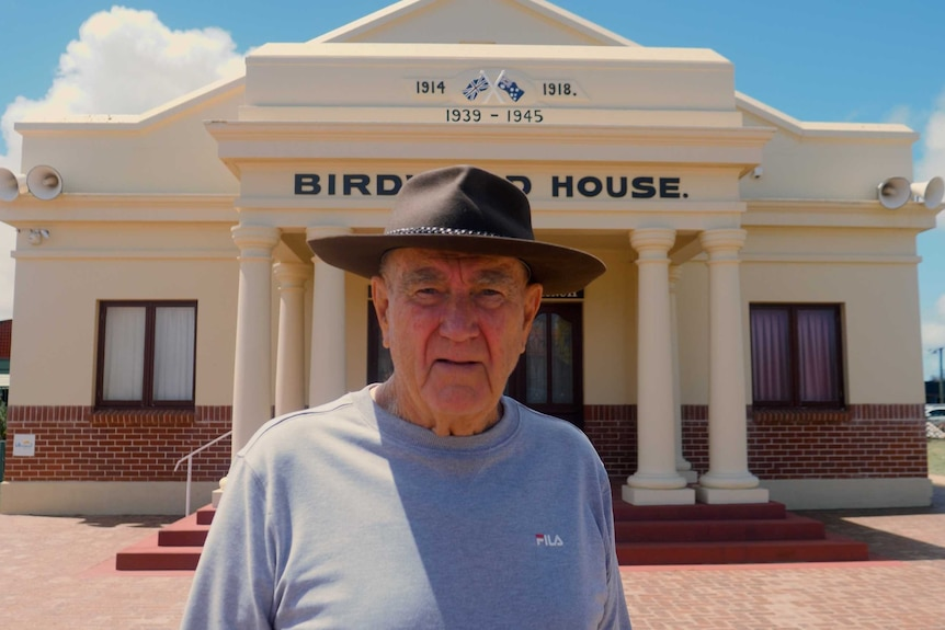 "A man with an Akubra-style hat stands outside a building with the years ""1914 - 1918 and 1939 - 1945""."