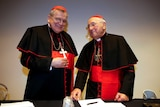 Two older white men wearing black cardinal robes, crosses and red caps.