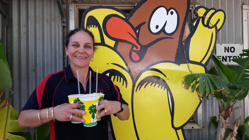 Jo Bumbak holding smoothies in front of a banana sign