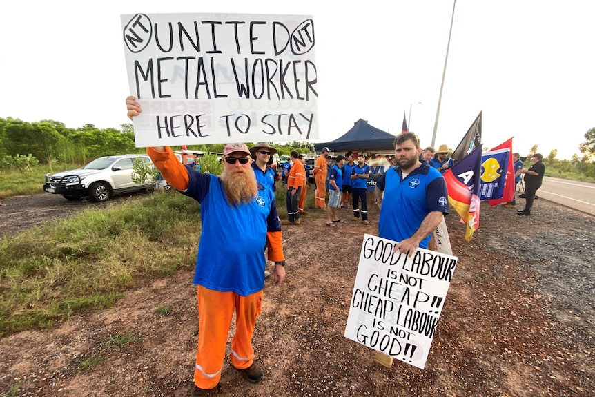 Men in high-vis holding protest signs by the side of the road.