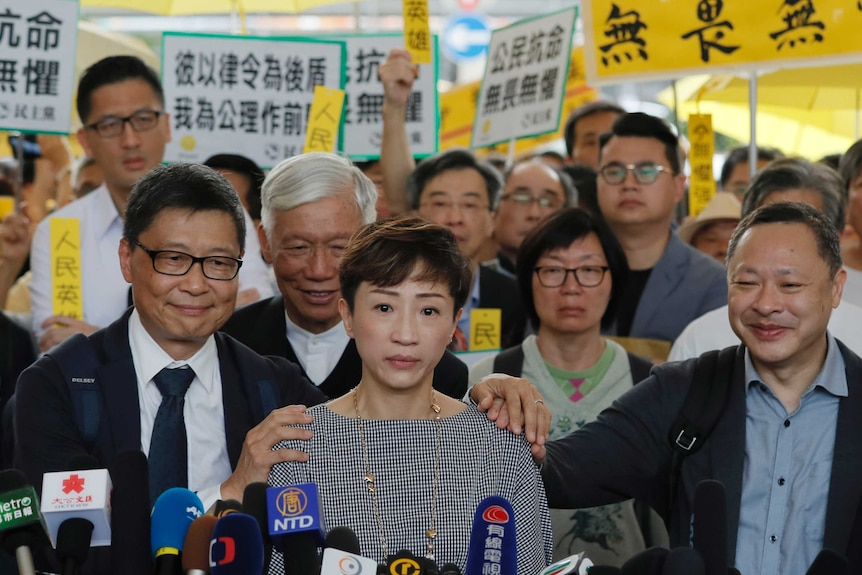 Tanya Chan in front of the microphones with Benny Tai, Chan Kin-man and Chu Yiu-ming surrounded by supporters with placards.