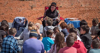 With red sand in the background, a woman sits in a deck chair reading a book to a group of children sitting, facing her.