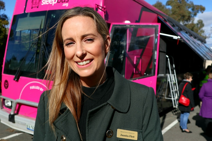 A young woman smiles at the camera in front of the pink Sleepbus.
