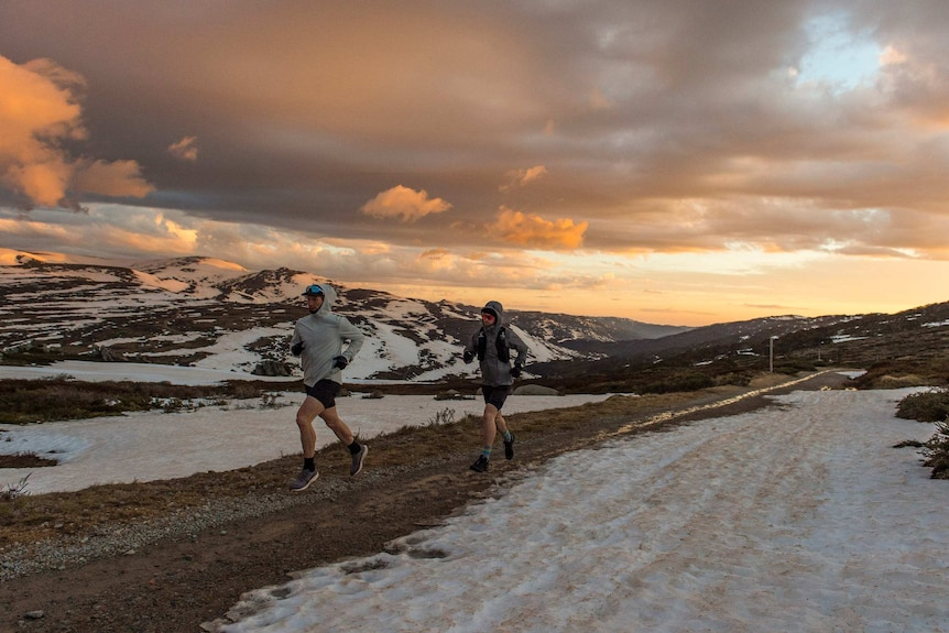 two men running on mountain surrounded by snow and orange sunrise