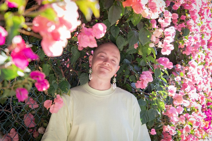 Man smiling surrounded by flowers.