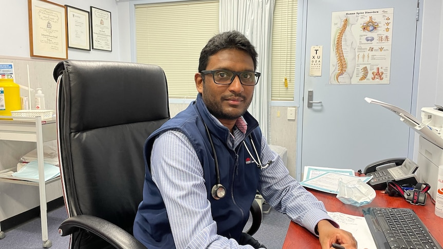 A doctor sits at his desk with a picture of a spine on the door behind him