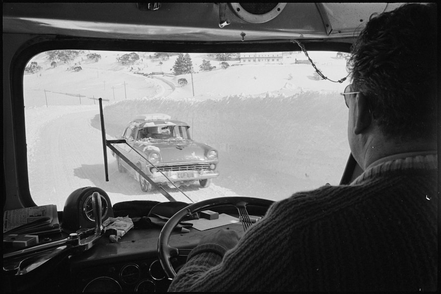 Black and white image from inside a vehicle looking out onto snow banks