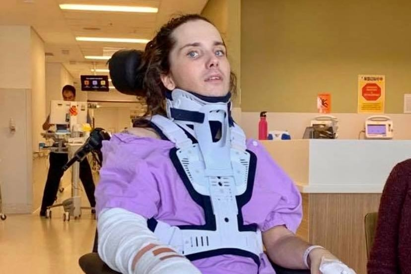 A young woman in a neck brace, sitting in a wheelchair.