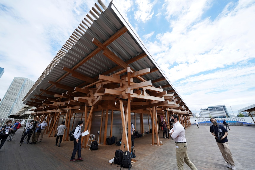 Journalist walk at the Village Plaza made up of timber beams near Tokyo 2020 Olympic and Paralympic Village