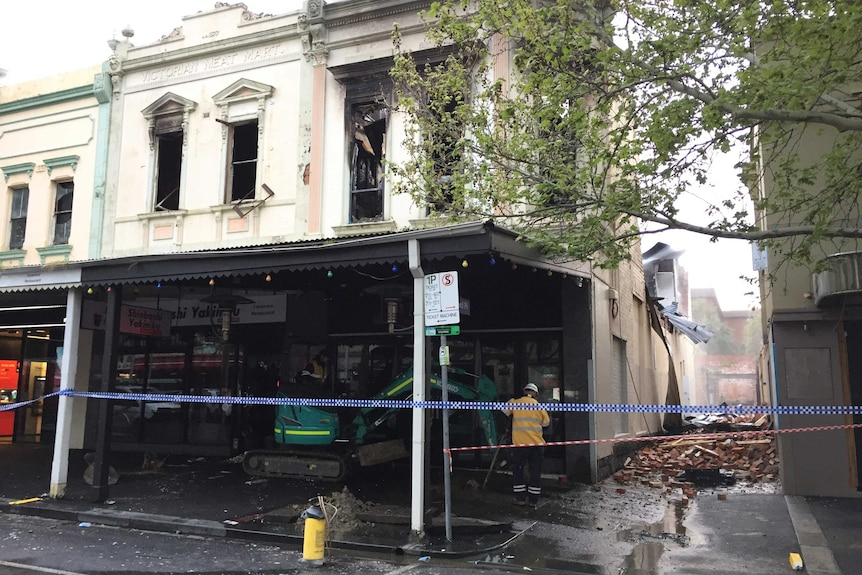 Police tape surrounds a gutted restaurant and debris-filled laneway.