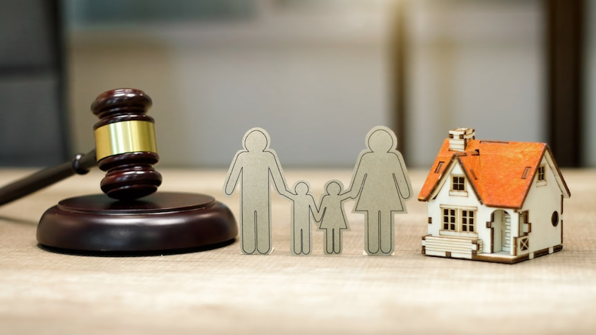 Cardboard cutout of a family surrounded by a doll sized house and a gavel.