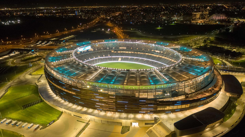 An aerial shot of Perth Stadium lit up at night.