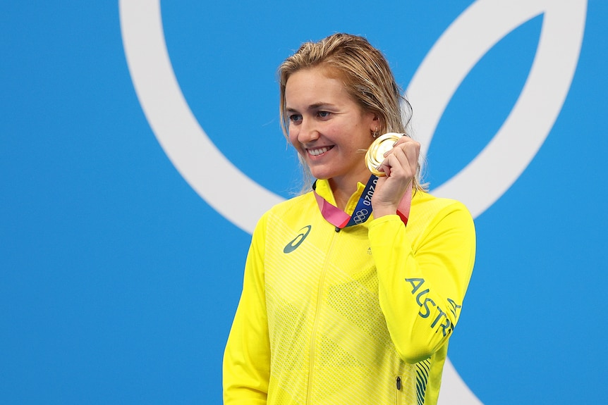 A blonde woman wearing a yellow jacket stands holding a gold medal