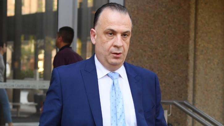 A man in a suit walks outside a courthouse.