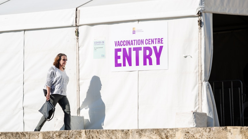 """A woman walks past a tent with a sign reading """"vaccination centre entry""""."""