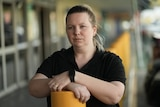 A woman wearing a black shirt folds her arms in from of a shopping centre.