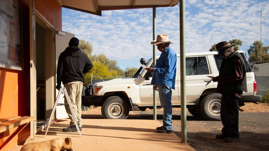 Three people stand in a line to vote in a remote community in the Northern Territory.