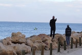 Two men standing near rocks onshore look out to sea, one of them pointing to the horizon as a small boat moves across the water.