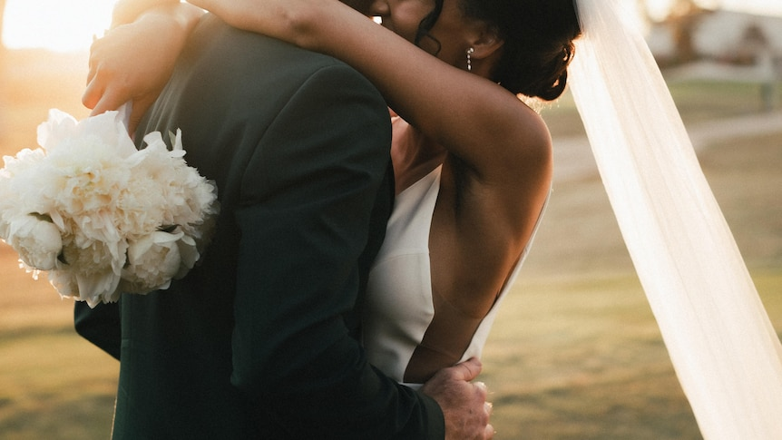 Interracial couple embracing on their wedding day in a story about falling in love with someone outside your culture.