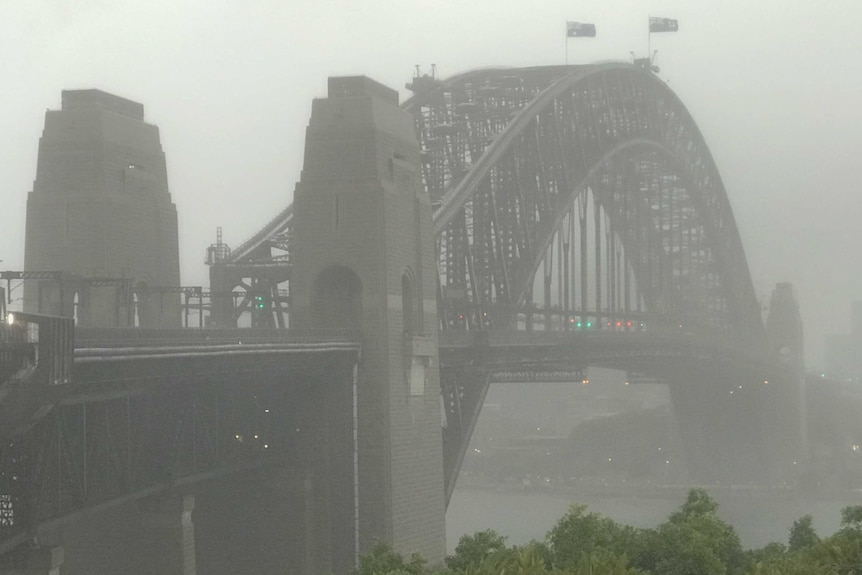 The Sydney Harbour Bridge stands amid a grey sky as torrential rain batters the city.