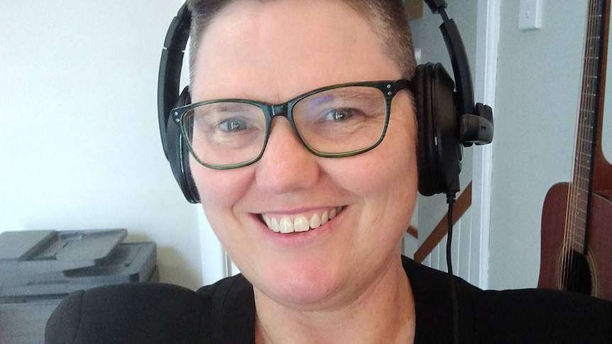 A woman with cropped hair wears glasses and heaphones while smiling.