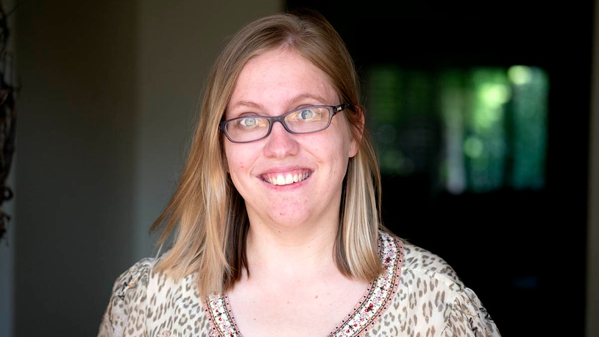 A woman wears glasses and smiles at the camera.
