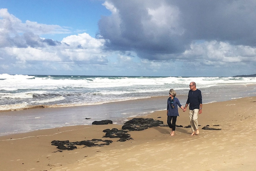 Nola Droop and her husband walk on the beach